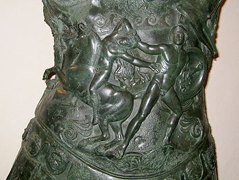 a piture beaten out on the bronze of the breastplate. A man with a shield drags a naked youth by the hair from his horse.