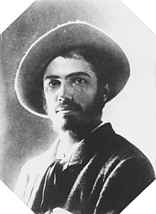 Black and white portrait photograph of Adolphe Appia in his twenties. He is dark haired and bearded and is wearing a hat with a big round brim.