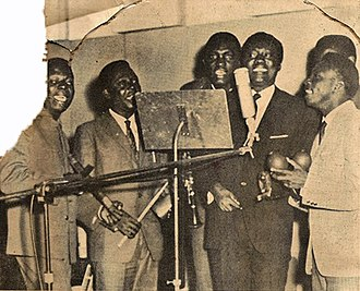 Congolese rumba - African Jazz in a recording studio in 1961. Joseph Kabasele is just to the right of the microphone.