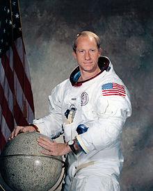 Alfred Worden portant une maquette de Lune dans ses main, devant un drapeau américain.