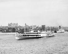 Una nave a vapore bianca è vista vicino alla riva del fiume Hudson di fronte al centro di Albany;  sullo sfondo si può vedere il Campidoglio dello Stato di New York.
