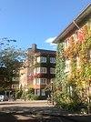 foto van Harmoniehof: gesloten en meerzijdig bouwblok op onregelmatig grondplan met individuele achtertuinen