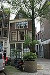 foto van Huis met latere gevel onder rechte lijst waarboven een bakstenen punttop