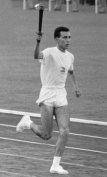 Athlete in white shorts and T-shirt running on an athletics track with the Olympic torch aloft in his right hand.