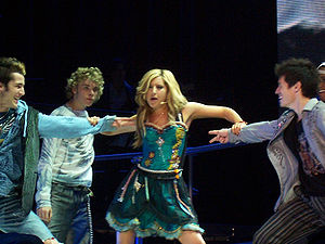 """Headstrong (Ashley Tisdale album) - Tisdale, flaunted by background dancers, performing """"Headstrong"""" during High School Musical: The Concert"""