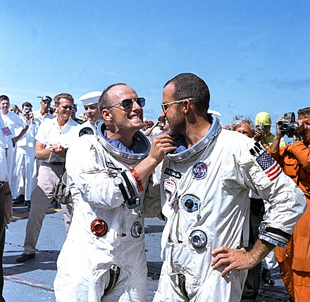 Pete Conrad (left) and Cooper on deck of recovery carrier USS Lake Champlain after Gemini 5 mission Astronaut Charles Conrad Jr. tweaks astronaut L. Gordon Cooper's eight-day growth of beard for the cameramen.jpg