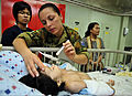Australian Army Capt. Kerry McKinnell, top center, checks the vitals of a four-month-old Indonesian girl who had surgery to fix her cleft lip aboard Military Sealift Command hospital ship USNS Mercy (T-AH 19) 120602-O-ZZ999-011.jpg
