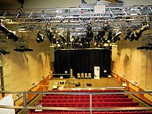 View of a theatre stage from the centre of the balcony. The stage is in the middle of being prepared for an event; there are chairs, microphones and foldback speakers in place. The top of the photograph features the theatre's lighting rig, above the auditorium. The theatre's red stalls seats are visible.
