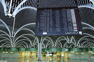 Baghdad International Airport - Inside view of the terminal in 2003, showing an abandoned and nonfunctional FIDS (note the red and white icon for the long-defunct East German airline Interflug in the fourth row from the bottom), in front of empty check-in desks and passport control