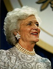 Barbara Bush, wearing pearls and a dress, is shown smiling