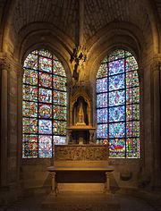 Photographie contemporaine d'un reliquaire de pierre situé entre les vitraux colorés d'une petite chapelle.