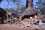 A Bedik village with a traditional house and two women working.