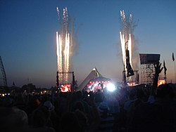 A large crowd is gathered round a stage, fireworks are in the sky.