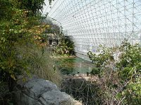 Biosphère II vue de l'intérieur, la savane au 1er plan et l'océan dans le fond.
