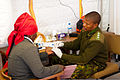 Botswana Defence Force Capt. Thapelo Dikolobe, right, a laboratory technician, performs basic blood testing during the second of four humanitarian civilian assistance events as part of Southern Accord 2012 120809-Z-LQ368-024.jpg