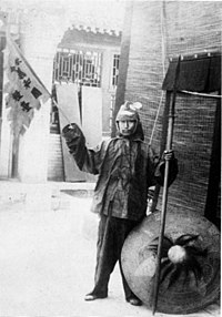 "A Boxer rebel. His banner says ""欽令 義和團糧臺"", ""By Imperial Order - Boxer Supply Commissariat""."