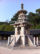 A stone pagoda with elaborated tiers, a small lion status, and stairs. Blue skies and a roof of a building and trees are shown on the background