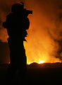 CAMP FALLUJAH, Iraq - Sgt. Robert B. Brown from Fayetteville, N.C. with Regimental Combat Team 6, Combat Camera Unit takes a photograph of civilian Fire Fighters at the burn pit as smoke and flames rise into 070525-M-SK703-009.jpg