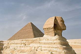 Old Kingdom of Egypt - The Great Sphinx of Giza in front of the Great Pyramid of Giza.