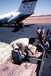 Capt. Stephen Foote, airlift commander from the 6th Military Airlift Squadron, helps workers load a truck with food during the Ethiopian relief operations DF-ST-86-11388.jpg