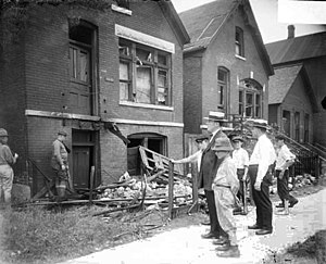 Chicago race riot of 1919 - White men and boys standing in front of vandalized house.