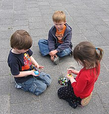 Three children aged about six years are in a group on the ground, a boy and girl kneeling and another boy seated cross-legged. The two kneeling children hold marbles. There are other marbles in a bag on the ground, they appear to be negotiating over the marbles. The third child is watching.