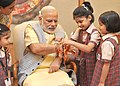 Children tying 'Rakhi' on the Prime Minister, Shri Narendra Modi's wrist, on the occasion of 'Raksha Bandhan', in New Delhi on August 29, 2015.jpg