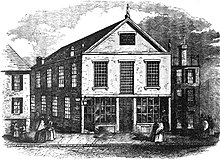 A black-and-white engraving of a street scene that depicts a 2.5-story church with mullioned windows at center.