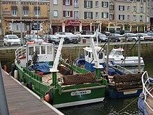 deux petits bateaux de pêche colorés dotés d'un filet enroulé à l'arrière