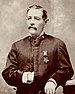 A white man with a mustache standing with his left arm resting on an object to his side and his right hand inside his jacket. A star-shaped medal is hanging from a ribbon on his left breast.