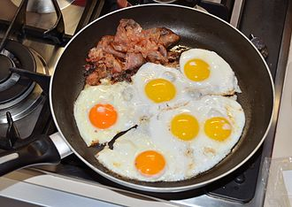 Egg as food - Bacon and eggs being cooked in a skillet.