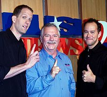 Three men all face forward and are smiling. Two of the men are extending their pointer fingers while the third man is giving a thumbs up gesture.