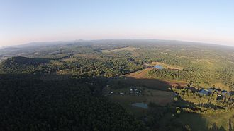 Amissville, Virginia - Drone aerial image from approximately 1,500 feet of altitude showing a portion of the eastern side of Battle Mountain, with Little Battle Mountain shown in the background on left. Camera is facing northeast in the direction of the Amissville post office (approximately 4 miles away, not shown). The sun is setting over the mountain to the west. Summer, 2015.