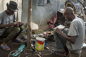 Economy of the Comoros - Informal sector: two men repairing electronical device.