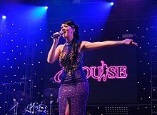 "Photograph of the singer Elouise performing on stage at London's ""Under the Stars"" concert"