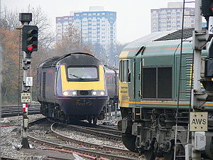 Railway signalling - The freight train (right) is waiting at a red signal while the passenger train (left) crosses its path at a junction.