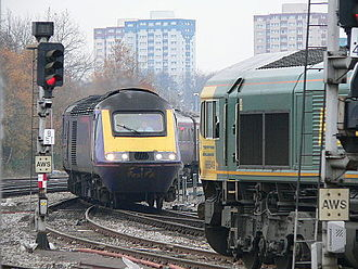 Railway signalling - A Class 66 locomotive (right) is waiting at a red signal while a First Great Western passenger train (left) crosses its path at a junction.