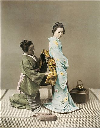 Obi (sash) - A Japanese woman tying the obi for a geisha in the 1890s.