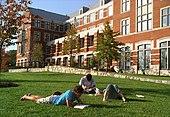 Tři mladí dospělí leží na trávě před knihami před cihlovou budovou s mnoha okny.