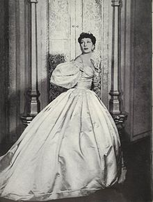 Woman looking over her shoulder, wearing a Victorian-style gown with a fitted bodice and full hoop skirt