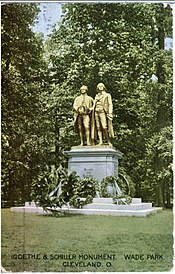 "Picture postcard of a large bronze statue of two men on top of a stone pedestal. There are several wreaths that have been placed at the base of the pedestal; the statue is standing in a grassy clearing in front of trees. There is printing along the bottom of the postcard that says ""Goethe and Schiller Monument, Wade Park, Cleveland, O."""