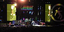 "A man wearing a hat is captured on two screens running across a stage as several musicians perform in front of an audience. ""GREENDAY"" is seen flashed in multi-colored letters on another screen."