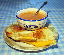 A bowl of soup and a cut sandwich on a plate