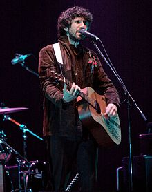 A man with long, bushy dark brown hair and a short beard playing acoustic guitar while singing into a microphone and looking to his right, away from the camera. He is seen from the knees upwards and is wearing a brown jacket with a red and blue embroidered pattern on the right shoulder.