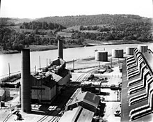 A large dark-coloured rectangular building and a smaller building with three smokestacks. In the background is the river. The steam plant is a small building with two smokestacks.