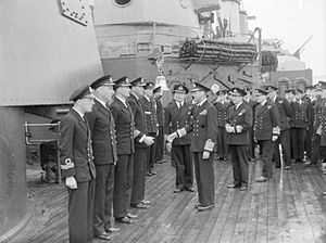 HMS London (69) - HM King George VI meeting the officers of HMS London lined up on deck next to one of the cruiser's 8-inch gun turrets, part of the Home Fleet at Scapa Flow.