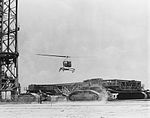 Helicopter hovering near a crawler-transporter (68-H-530).jpg