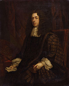 A dour-looking man sitting in a simple, studded, leather chair. He is wearing an ornate black robe with gold trim, and possibly a large brown wig, although that may be his hair. In his hand is a piece of paper.