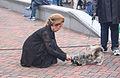 Hurkende oude vrouw met hond.jpg