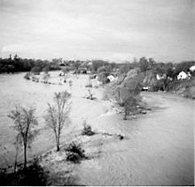 A generally flat area is completely submerged by water; trees are scattered throughout.